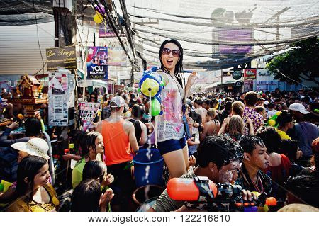 KO SAMUI, THAILAND - APRIL 13: Unidentified girl shooting water at the camera on Songkran Festival (Thai New Year) on April 13, 2014 in Chaweng Main Road, Ko Samui island, Thailand.
