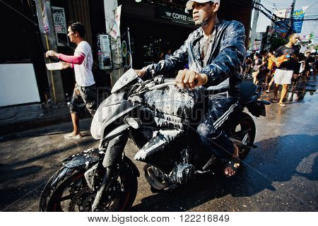 KO SAMUI, THAILAND - APRIL 13: Unidentified dirty biker in a water fight festival or Songkran Festival (Thai New Year) on April 13, 2014 in Chaweng Main Road, Ko Samui island, Thailand.