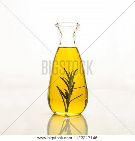Olive oil flavored with rosemary in glass bottle isolated on white background.