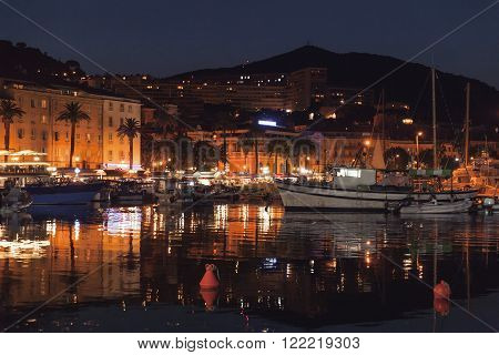 Pleasure yachts and fishing boats moored in old port of Ajaccio the capital of Corsica island France. Night photo poster