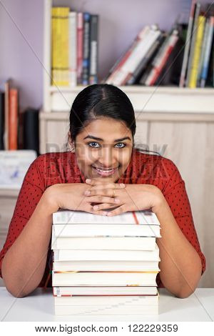 Young pretty india woman sitting at a table, hands on a staple of books, looking happy at camera, vertical
