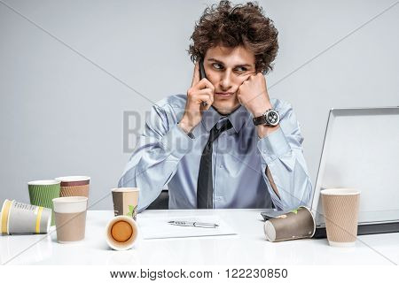 Young business man talking on the phone / businessman at the workplace working, depression and crisis concept