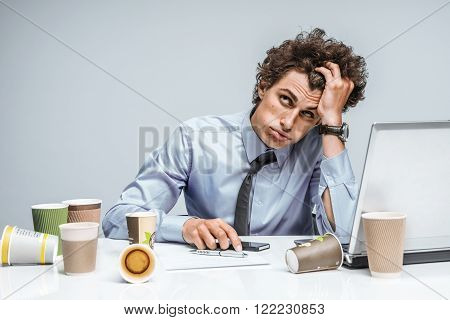 Distressed young manager man holds her head with hand. Modern office man at working place depression and crisis concept