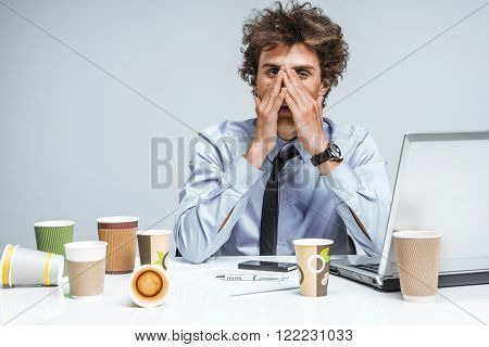 Exhausted man closed his eyes with his hands. Young student with lot of work education concept