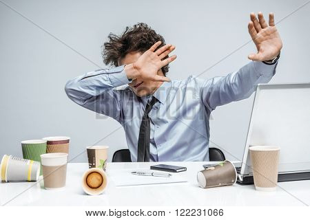 Shocked businessman with eyes closed is against uncensored Internet content / overwhelmed businessman close his eyes and turned away from the laptop screen