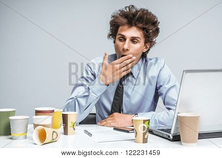 Tired man yawns and covers her mouth with her hand / modern office man at working place, depression and crisis concept