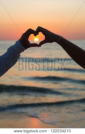 Couple doing heart shape with their hands on beachside sunset.