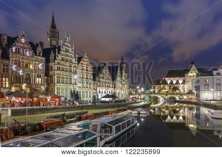 Picturesque medieval building and St Michael's Bridge on the quay Graslei in Leie river at Ghent town at night, Belgium