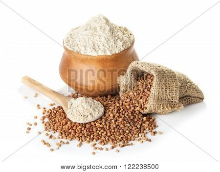buckwheat flour in bowl and a bag a wooden spoon isolated on a white background closeup