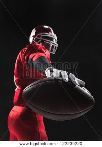 Caucasian fitness man as american football player holding a ball on black background