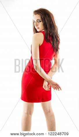 Beautiful young brunette model in red dress with crossed hands behind her back. Side view. Isolated on a white background.