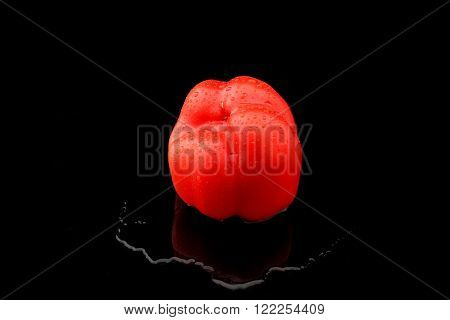 a red paprika with water on black background