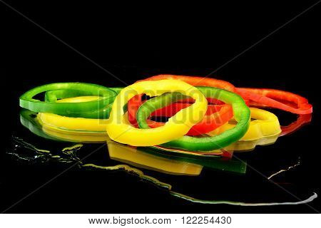 a heap sliced peppers on black background with water