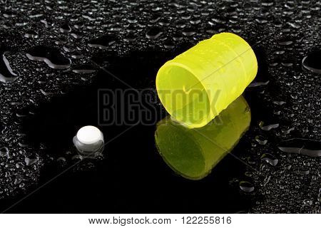 a white tablet with a yellow cup on water drops