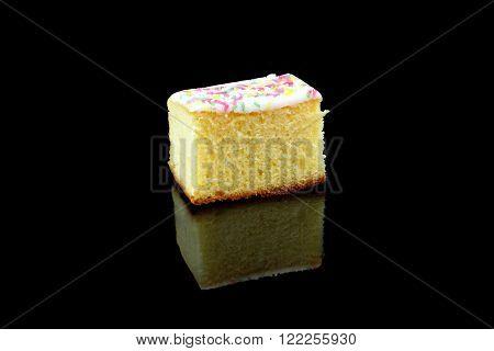 a piece of lemon cake on a black background
