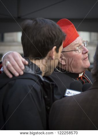 NEW YORK - MAR 17, 2016: Timothy Cardinal Dolan Archbishop of New York looks to the sky while talking to a parade goer by St Patricks Cathedral on St Patricks Day in Manhattan, March 17, 2016.