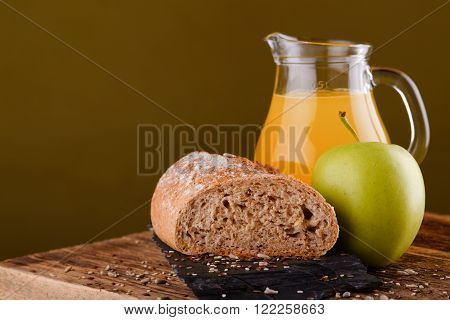 Loaf Of Bread On Black Stone With Apple And Juice
