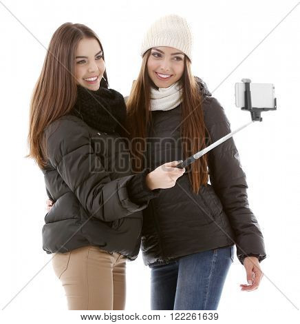 Two teenager girls in winter clothing making photo by their self with mobile phone, isolated on white