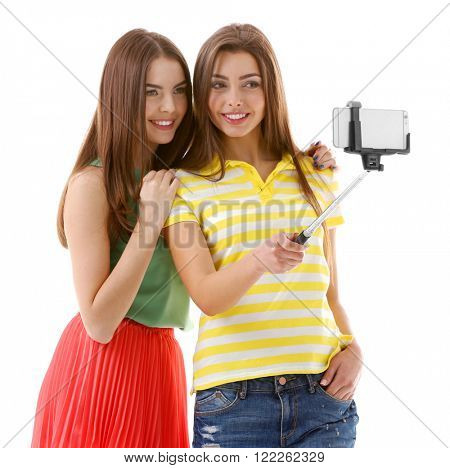 Two teenager girls making photo by their self with mobile phone, isolated on white