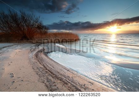 sunshine over beach on lake Ijsselmeer Netherlands