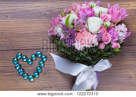 Valentine flowers with heartshaped jewellery on wooden background