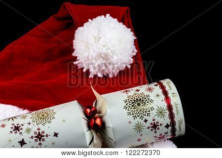 Christmas santa hat and traditional Christmas cracker on black background