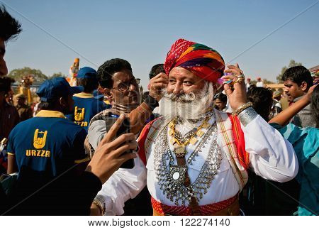 JAISALMER. INDIA - Feb 1: Handsome senior man with great mustaches in Rajput costume has fun in crowd of the Desert Festival on February 1, 2015. Every winter Jaisalmer takes famous Desert Festival