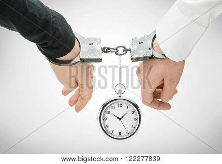 Hands of two men fixed in handcuffs. Pocket wartch between them. Close up. Concept of accessory of crime.