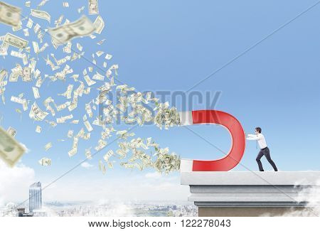 Businessman on roof with magnet pulling dollars. City and sky at background. Concept of attracting money.