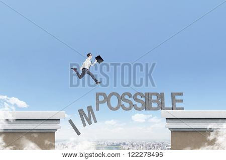 Businessman running over word 'impossible' between two roof letters I and M falling down. Blue sky at background. Concept of opportunity.