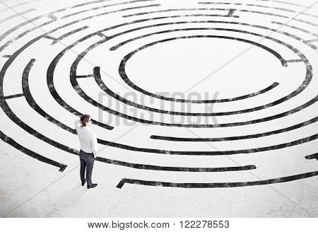 Businessman with hand on head standing on white floor in front of painted labyrinth. Concept of finding solution.