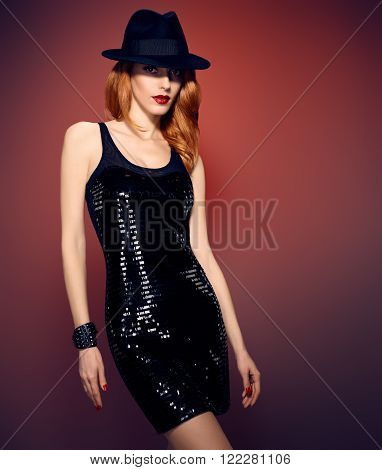 Fashion portrait of sexy beauty woman in stylish sequins dress and black hat. Unusual creative provocative. Emotional playful redhead glamour girl, luxury evening elegant party style on red, people