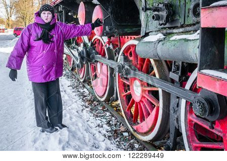 Pretty woman and Old steam locomotive wheel and rods