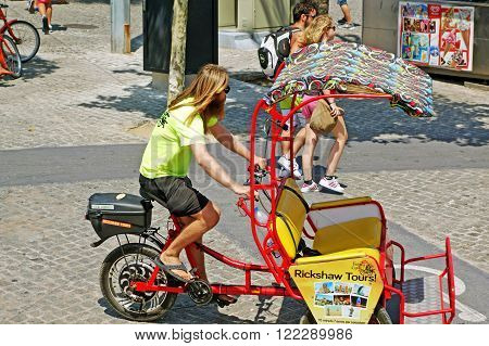 BARCELONA, SPAIN - JULY 31, 2015: A young man ride a rickshaw taxi in Barcelona. Rickshaw taxis offer unique group tours through the city and a funny form of transport among locals and tourists.