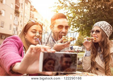 Group of young people laughing and doing a selfie in cafe.