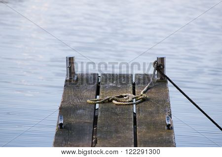 wooden jetty for boats and an old rope in the blue water background with copy space selected focus narrow depth of field