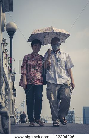 Bangkok Thailand - March 05 2014: Street portrait of an older couple with umbrella one wearing a mask. Bangkok Air pollution reaches a critical level.