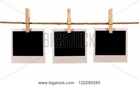 Several blank instant photo print frames hanging on a rope or washing line white background