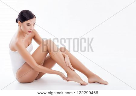 Body of attractive healthy girl applying cream on her heels. She is sitting and looking at her skin with joy. Isolated on white background and copy space in right side