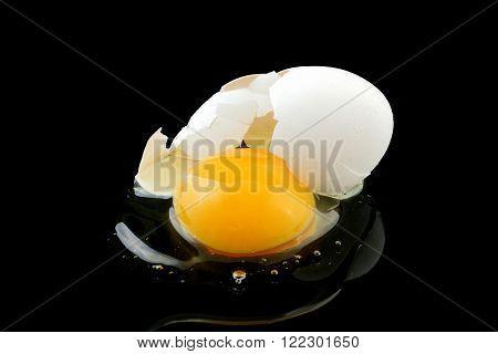 a broken egg on a black background