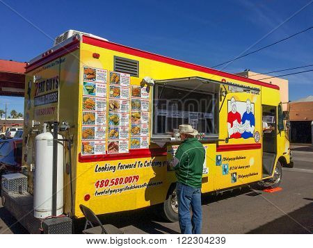 PHOENIX AZ - FEBRUARY 5 2016: A man buying lunch from Two Fat Guys Grilled Cheese food truck at designated outdoor spot in downtown of Phoenix AZ