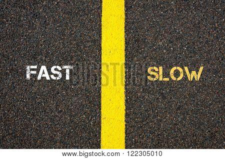 Antonym concept of FAST versus SLOW written over tarmac road marking yellow paint separating line between words poster