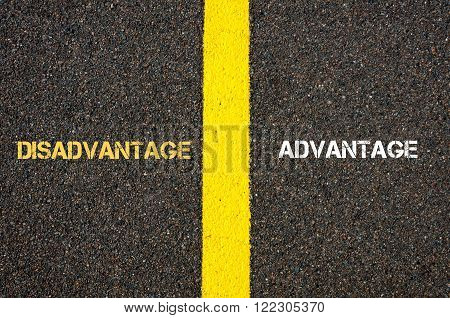 Antonym concept of DISADVANTAGE versus ADVANTAGE written over tarmac road marking yellow paint separating line between words poster