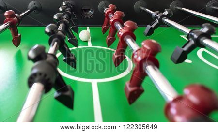 table soccer or table football black and red figures on green.