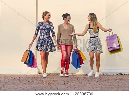 Walking around. group Women walking with Shopping Bags On City Street against wall