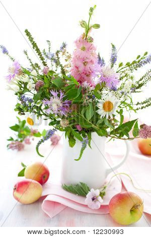 bunch of wild herbs, flowers in a  jug and apples