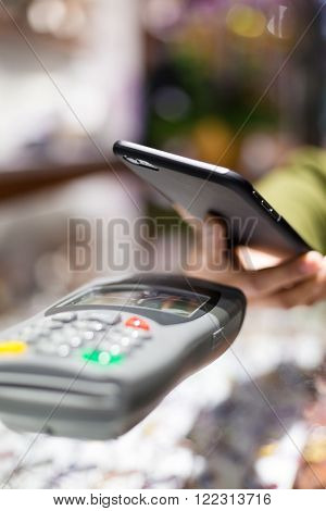 Woman paying with NFC technology on celphone