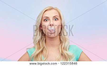 emotions, expressions and people concept - happy young woman or teenage girl chewing gum over rose quartz and serenity gradient background