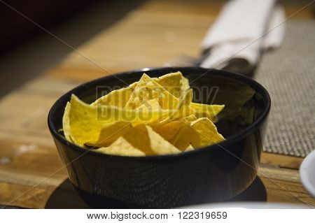 Nacho chips served in a black bowl