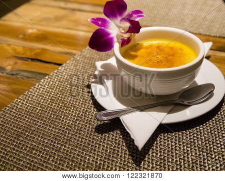 Creme brulee served with a frangipani flower